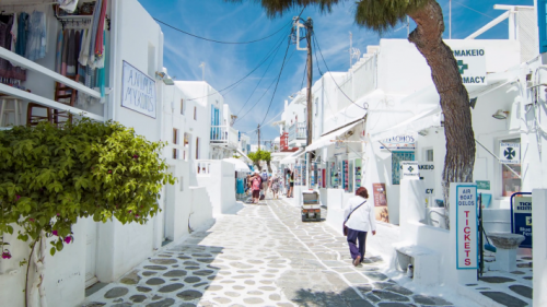 town-streets-of-mykonos-greece-in-between-white-buildings-with-shopping-and-sigh.png